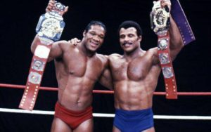 Teddy Atlas and Rocky Johnson show off their WWF tag team belts.
