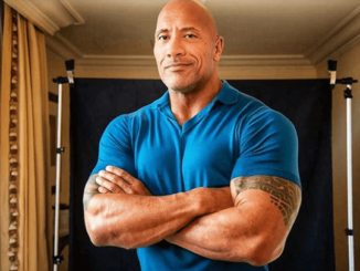 the rock dwayne johnson in a blue t shirt.