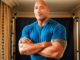 the rock dwayne johnson in a blue t shirt.